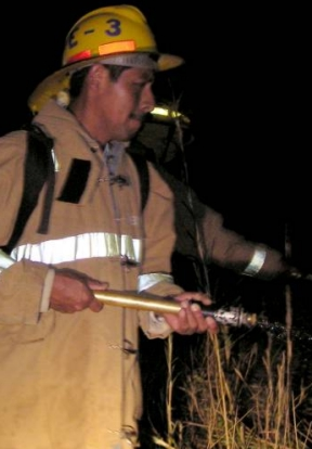 Bomberos fight fire in Volcan hills.