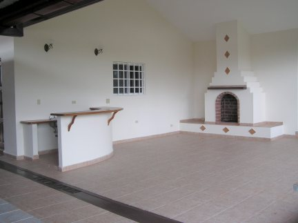 Large, tiled and covered patio overlooks ornamental garden