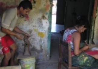 Beilka de Medoza paints while Carlos Calderon sculpts yet another piece for the local market.